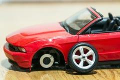 Primer de la vista posterior del coche rojo del juguete después del accidente de carretera Imagenes de archivo