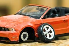 Primer de la vista posterior del coche rojo del juguete después del accidente de carretera Fotos de archivo