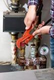 Primer de la válvula de torneado del sistema de calefacción del fontanero con los alicates rojos Imagen de archivo