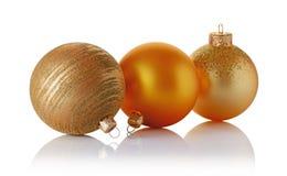 Primer de las bolas hermosas de la Navidad del oro con el modelo que brilla de oro Fotografía de archivo