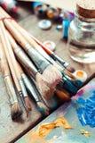 Primer de las brochas, paleta del artista y tubos multicolores de la pintura Imagen de archivo libre de regalías