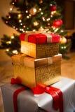 Primer de las cajas de regalo de oro y rojas debajo del árbol de navidad Imágenes de archivo libres de regalías