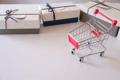 Primer de las cajas y del carro de la compra de regalo en el escritorio blanco fotografía de archivo
