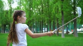 Primer de las chicas jóvenes despreocupadas que hacen los rodillos patinadores de los selfies en outdoo del parque Fotos de archivo libres de regalías