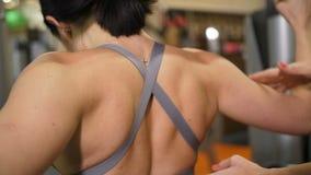 Primer de las cuchillas La muchacha delgada sacude los músculos de los brazos y detrás en el gimnasio 4K MES lento almacen de metraje de vídeo