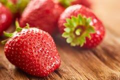 Primer de las fresas rojas frescas en la tabla de madera marrón Imagen de archivo