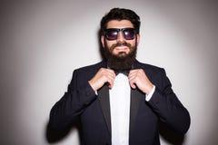 Primer de las gafas de sol que llevan hermosas del hombre joven que ajustan su corbata de lazo y que miran la cámara Fotografía de archivo