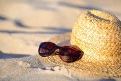 Primer de las gafas de sol y del sombrero de paja en la arena en la playa Fotografía de archivo