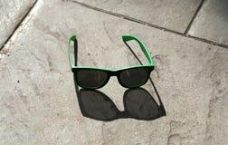 Primer de las gafas de sol que ponen en la tierra foto de archivo libre de regalías