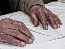 Primer de las manos arrugadas de la pluma y del papel de tenencia del hombre, llevando un suéter verde imagenes de archivo