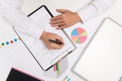 Primer de las manos de la empresaria, escribiendo en el papel Imagenes de archivo