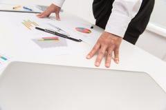 Primer de las manos de la empresaria que se inclinan en la tabla Fotografía de archivo libre de regalías