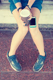Primer de las manos de la mujer joven con el teléfono y la taza de café elegantes Imagenes de archivo