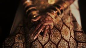 Primer de las manos de la novia india cubiertas con mehndi y sostener un collar de oro metrajes
