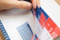 Primer de las manos de la persona del negocio que comprueban el calendario Fotos de archivo