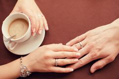 Primer de las manos de los pares de la boda y de la taza de café Fotografía de archivo libre de regalías