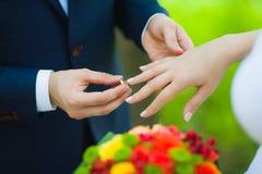 Primer de las manos de pares irreconocibles nupciales con los anillos de bodas la novia sostiene el ramo de la boda de flores Imagen de archivo