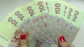 Primer de las manos de un hombre de negocios que cuentan cientos cuentas del hryvnia en una tabla metrajes