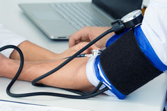 Primer de las manos del doctor que miden la presión arterial a su varón fotografía de archivo
