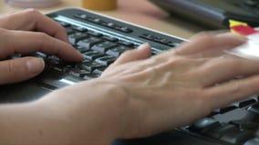 Primer de las manos del encargado que mecanografían en el teclado almacen de video