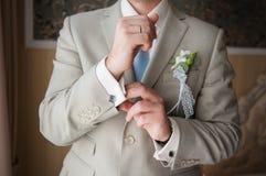 Primer de las manos del hombre de la elegancia con el anillo, la corbata y la mancuerna Foto de archivo libre de regalías