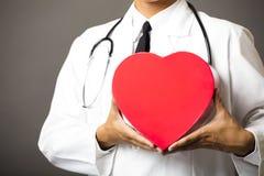 Primer de las manos del médico con el corazón Foto de archivo libre de regalías