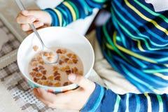 Primer de las manos del muchacho del niño que comen los cereales hechos en casa para el desayuno o el almuerzo Imagenes de archivo