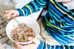 Primer de las manos del muchacho del niño que comen los cereales hechos en casa para el desayuno o el almuerzo Foto de archivo libre de regalías