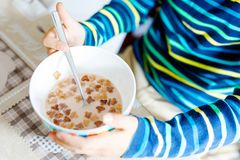 Primer de las manos del muchacho del niño que comen los cereales hechos en casa para el desayuno o el almuerzo Imágenes de archivo libres de regalías