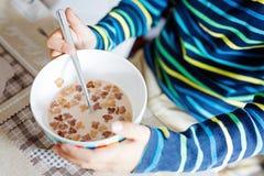 Primer de las manos del muchacho del niño que comen los cereales hechos en casa para el desayuno o el almuerzo Fotografía de archivo