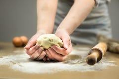 Primer de las manos del panadero de sexo femenino que amasan la pasta en panadería Foto de archivo libre de regalías