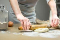 Primer de las manos del panadero de sexo femenino que amasan la pasta en panadería Fotografía de archivo libre de regalías