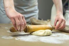 Primer de las manos del panadero de sexo femenino que amasan la pasta en panadería imágenes de archivo libres de regalías