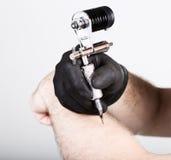 Primer de las manos del Tattooist en guantes negros con la máquina del tatuaje Fotografía de archivo
