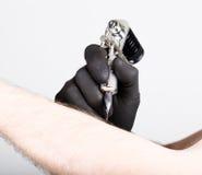 Primer de las manos del Tattooist en guantes negros con la máquina del tatuaje Fotografía de archivo libre de regalías