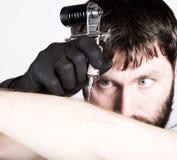 Primer de las manos del Tattooist en guantes negros con la máquina del tatuaje Foto de archivo libre de regalías