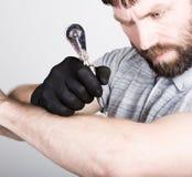 Primer de las manos del Tattooist en guantes negros con la máquina del tatuaje Imágenes de archivo libres de regalías