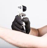 Primer de las manos del Tattooist en guantes negros con la máquina del tatuaje Foto de archivo
