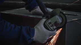 Primer de las manos del trabajador de sexo masculino en guantes de trabajo grises y el uniforme azul marino que muelen una esquin almacen de video