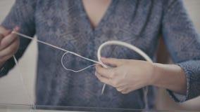Primer de las manos femeninas atadas con base redonda del hilo y de la armadura almacen de video