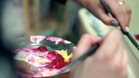 Primer de las manos femeninas del artista y de una paleta con las pinturas almacen de video