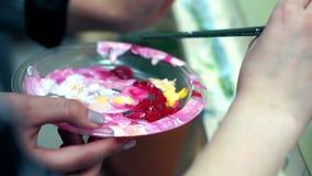 Primer de las manos femeninas del artista y de una paleta con las pinturas almacen de metraje de vídeo
