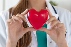 Primer de las manos femeninas del doctor que llevan a cabo el corazón leído foto de archivo libre de regalías