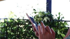 Primer de las manos femeninas jovenes que mecanografían SMS en el smartphone que se sienta en el balcón el vacaciones