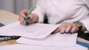 Primer de las manos femeninas que arreglan documentos en la mesa