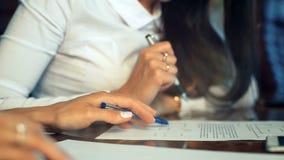 Primer de las manos femeninas que hacen notas en la libreta en la oficina durante entrevista metrajes