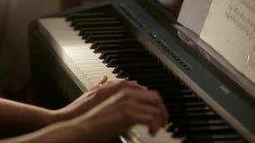 Primer de las manos femeninas que juegan el piano eléctrico metrajes