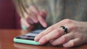 Primer de las manos femeninas que mecanografían el texto en un smartphone conectado con una red del wifi en un café metrajes