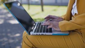 Primer de las manos femeninas que mecanografían en el teclado de ordenador outdoors Mujer de negocios joven en el traje que se si metrajes