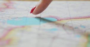 Primer de las manos femeninas que señalan en lugares del mapa del viaje a la visita El carro tiró del planeamiento del finger del almacen de video